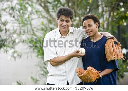 Hispanic father with African American teenage son holding baseball and glove