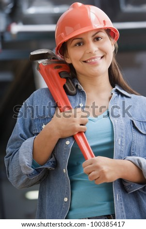 Hispanic female construction worker holding a wrench