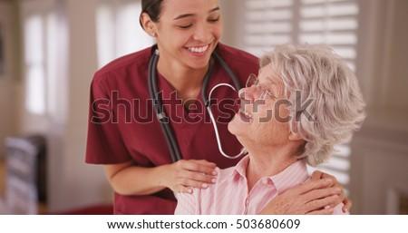 Hispanic female nurse looking and smiling with senior caucasian woman