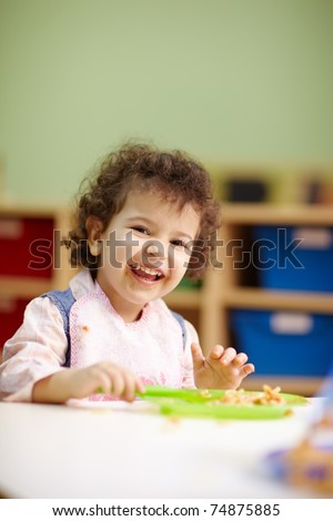 hispanic female preschooler eating pasta and smiling at camera. Vertical shape, waist up, copy space
