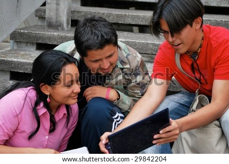 Hispanic friends looking at a computer together
