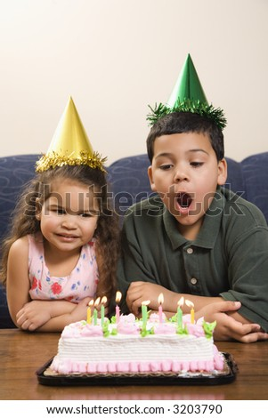 Hispanic girl and boy wearing party hats preparing to blow candles out on birthday cake.
