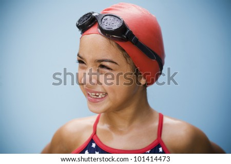 Hispanic girl in bathing suit with goggles and swim cap - stock photo