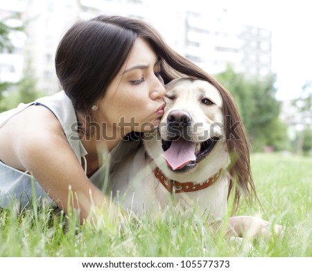 Hispanic girl kissing her dog in the park on the background of the house