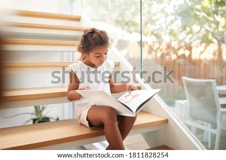 Hispanic Girl Sitting On Staircase In Modern Home Reading Book Сток-фото ©