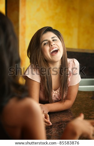 Hispanic girl with friend laughs out loud