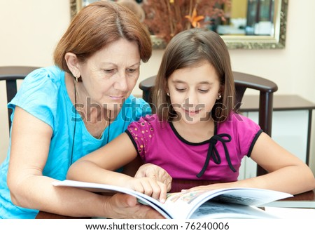 Hispanic grandmother and granddaughter reading an illustrated  book