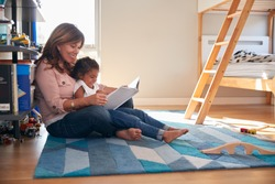 Hispanic Grandmother And Granddaughter Sitting On Floor Of Childrens Bedroom Reading Book Together