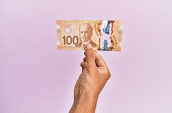 hispanic hand holding 100 canadian dollars banknote over isolated pink background.