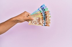 Hispanic hand holding canadian dollars banknotes over isolated pink background.
