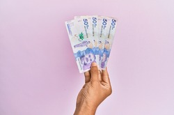 Hispanic hand holding 50 colombian pesos  banknotes over isolated pink background.