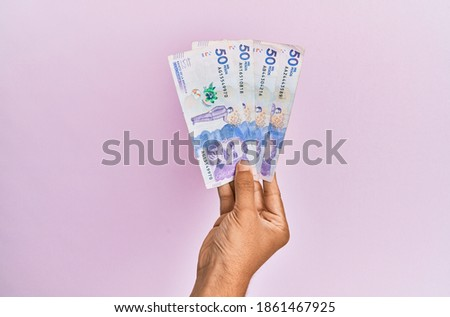 Hispanic hand holding 50 colombian pesos  banknotes over isolated pink background. Foto stock ©