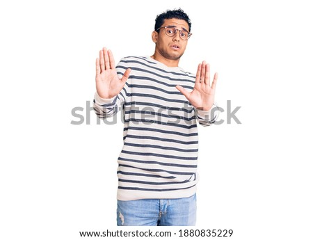 Hispanic handsome young man wearing casual clothes and glasses afraid and terrified with fear expression stop gesture with hands, shouting in shock. panic concept.  Foto stock ©