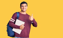 Hispanic handsome young man wearing student backpack and notebook smiling happy and positive, thumb up doing excellent and approval sign