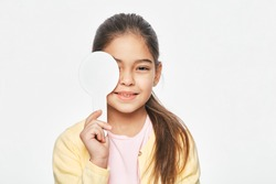 Hispanic little girl having eye exam with one eye covering using a special ophthalmic tool, on light grey background. Eye test for child