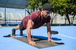 hispanic male athlete trainer working out with resistance bands, push ups and body weight training. Latin man training at a park on a sunny day for well beign