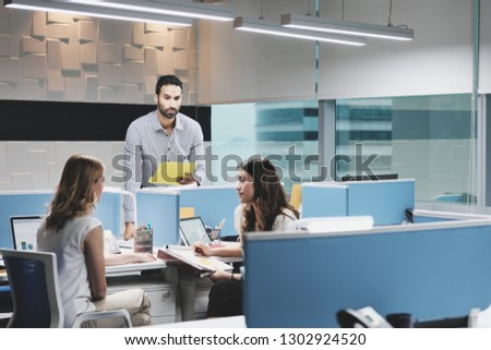 Hispanic male employee in modern coworking space, excluded by female colleagues. Adult businessman in hostile working environment, holding files and trying to catch coworkers attention. Photo stock ©