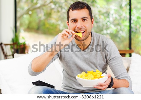 Hispanic male wearing light blue sweater plus denim jeans sitting in white sofa holding bowl of potato chips and remote control watching tv enthusiastically.