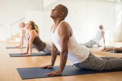 Hispanic man practicing yoga postures during group training at gym, performing stretching asana Urdhva Mukha Shvanasana (Upward Facing Dog Pose)