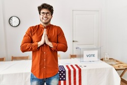 Hispanic man standing by election room begging and praying with hands together with hope expression on face very emotional and worried. begging.