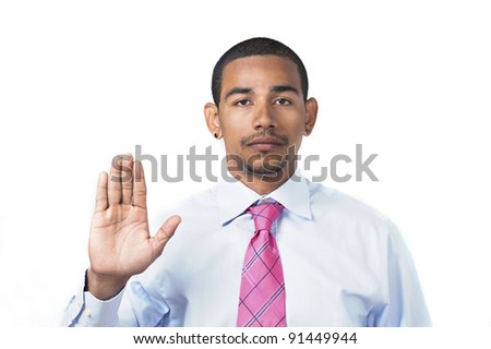 Hispanic man taking oath or pledge with right hand raised and serious expression