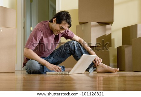 Hispanic man typing on laptop in new house - stock photo