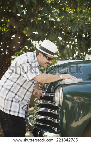 hispanic man waxing truck