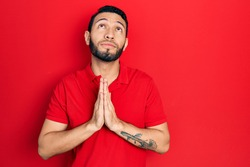Hispanic man with beard wearing casual red t shirt begging and praying with hands together with hope expression on face very emotional and worried. begging.