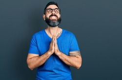 Hispanic man with beard wearing casual t shirt and glasses begging and praying with hands together with hope expression on face very emotional and worried. begging.