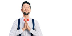 Hispanic man with beard wearing hipster look with bow tie and suspenders begging and praying with hands together with hope expression on face very emotional and worried. begging.
