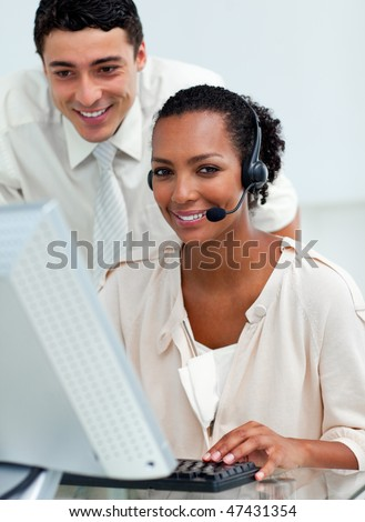Hispanic manager checking his employee's work at a computer