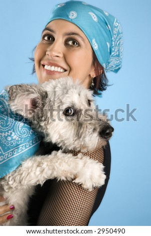 Hispanic mid-adult woman holding small white dog wearing matching bandanas.