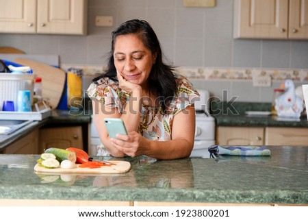 Hispanic mom searching recipes on her phone-woman preparing healthy and organic salad while checking her cell phone-bored housewife while she looks at her phone