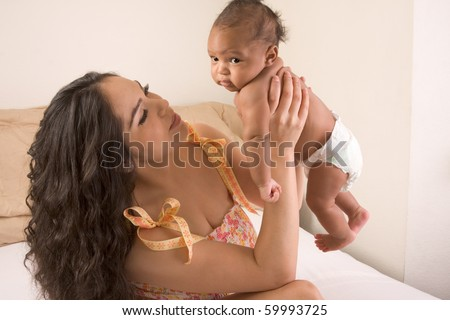 Hispanic mom sitting on bed and holding her biracial mix of Hispanic and African American infant son (baby is 7 weeks old)