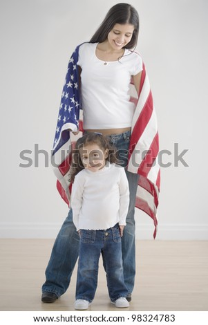 Hispanic mother and daughter holding American flag
