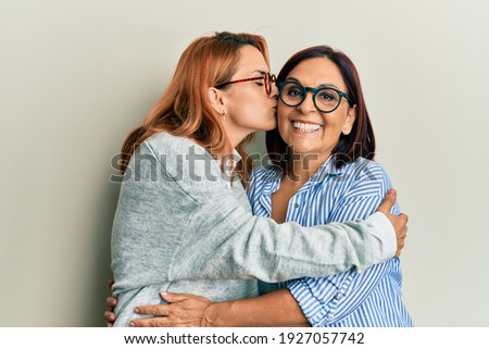 Hispanic mother and daughter smiling happy. Standing with smile on face hugging and kissing over isolated white background. Stok fotoğraf ©