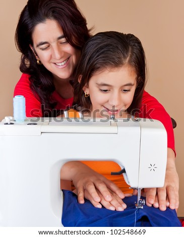 Hispanic mother  and her daughter using a sewing machine and sharing a good time together