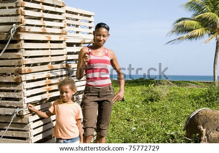 Hispanic mother daughter by lobster pot traps Caribbean Sea Big Corn Island Nicaragua Central America