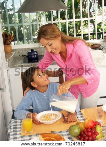 Hispanic mother pouring milk and cereal corn to her daughter.