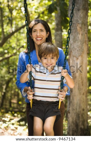 Hispanic mother pushing son on swing and smiling at viewer.