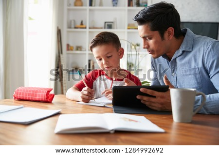 Hispanic pre-teen boy sitting at dining table working with his home school tutor
