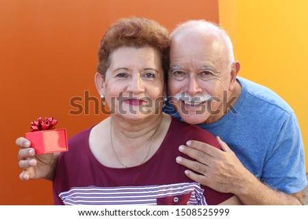 Hispanic senior surprising his loved one with a gift  #1508525999