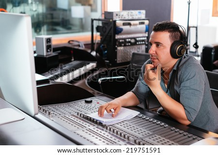 Hispanic sound engineer working at mixing panel in the recording studio