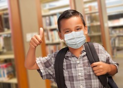 Hispanic Student Boy Wearing Face Mask with Thumbs Up and Backpack in the Library.
