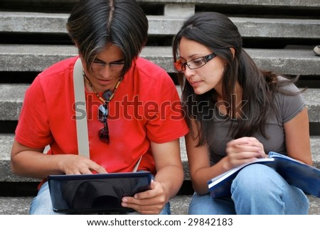 Hispanic students looking at a laptop together