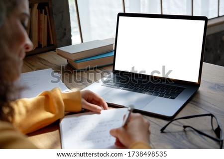 Hispanic teen girl, latin young woman school student elearning distance training course work at home office watching online learning webinar using laptop. Over shoulder close up mock up screen view.
