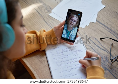Hispanic teen girl school pupil college student wear headphones hold phone learning online with math teacher tutor using mobile video conference call app write in workbook. Over shoulder closeup view.