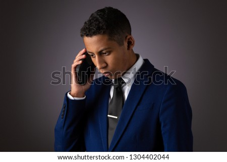 Hispanic Teenager Dressed Well Dressed in Suit, and Using Cellphone, Smartphone #1304402044