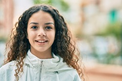 Hispanic teenager girl smiling happy standing at the city.