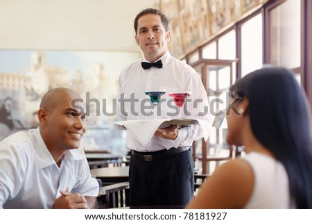 hispanic waiter serving adult couple at table in restaurant and looking at camera. Horizontal shape, front view, waist up